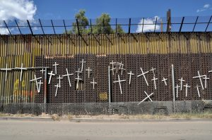 """The city of Nogales is divided in two by the Mexico-US border. This photograph shows the Mexican side, commemorating those who have died trying to cross into the United States.  Jonathan McIntosh, """"Wall of Crosses in Nogales,"""" 2009. CC BY 2.0, via Flickr."""